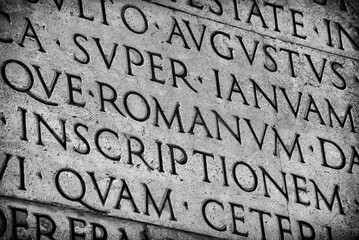Latin ancient language and classical education. Inscription from Emperor Augustus famous Res Gestae (1st century AD), with the word Romanum in the center (Black and White)