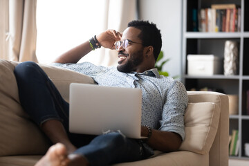 Single guy resting on couch with pc, internet user distracted from laptop usage looks at window...