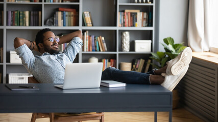 Carefree African male employee enjoy pause during workday leaned on office chair puts legs on desk looking out the window feel good. Lazy guy daydreams about future achievements, career growth concept