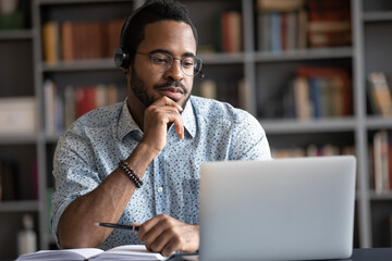 Focused African man wear headphones with microphone looking at laptop screen listens audio lesson...