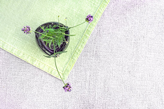 Lilac glass vase with lavender flowers on linen textile background.