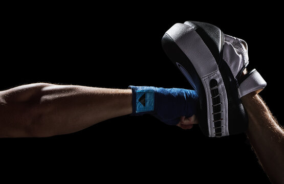 Boxing punch in to Punch Mitts. Training pad. Fighter athlete  wrapped hand is punching with fist and bare knuckles. Isolated on a black background.