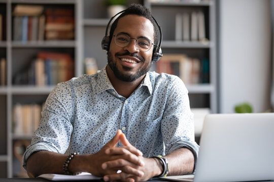 African man wear headset sit at workplace desk smile looking at camera, company consultant portrait, distant communication with client. Easy interesting e-learn study, online modern app usage concept