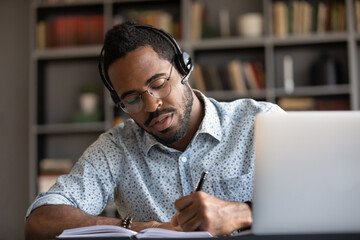 Focused young serious african ethnicity businessman wear headset writes notes in notebook watching...