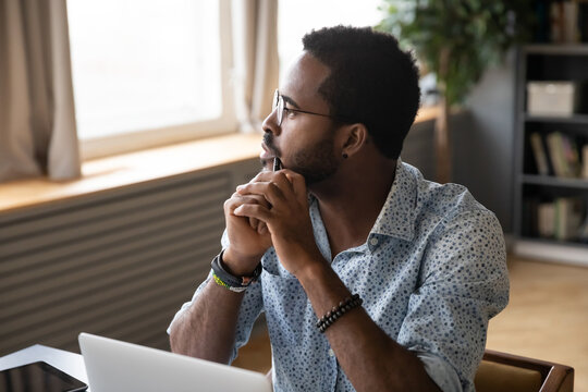 African guy sitting at table near laptop pondering over problem search answer looking at distance out the window. Student or office worker having doubts, feel uncertain thinking about solution concept