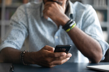 African guy holds cell phone close up view hands and device man feels concerned on background,...