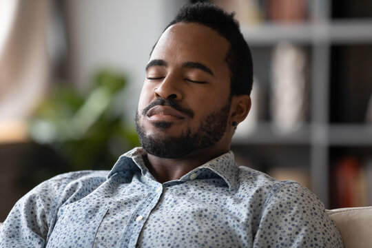 Close up African young man sit on couch closed eyes resting reduces fatigue, enjoy lazy day, breath fresh air at conditioned home, visualizing and meditating improve inner balance, no stress concept