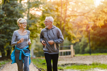 Self adhesive Wall Murals Jogging Smiling senior couple jogging in the park
