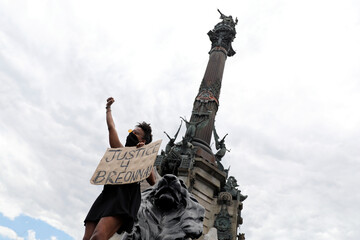 A woman holds a sign as she shouts slogans underneath the Columbus Monument during a protest against the death in Minneapolis police custody of African-American man George Floyd, in Barcelona