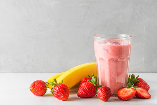 Glass of strawberry and banana smoothie or milkshake with fresh fruits and berries. refreshing summer drink