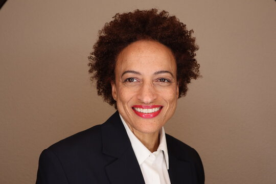 Smiling beautiful african american woman with natural hair wearing a dark suit and white shirt.