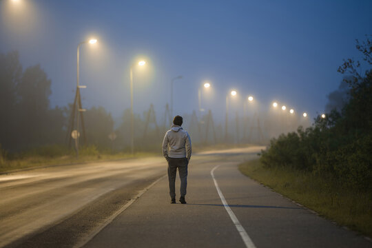 One young man slowly walking on long sidewalk under street lights in summer night. Spending time alone. Back view.