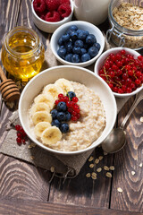 homemade oatmeal with berries on wooden background, vertical top view