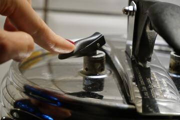 Woman depressurizing pressure cooking pushing on the safety valve