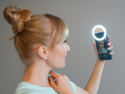 stylish beautiful blonde woman blogger making selfie with her smartphone and selfie ring. Trend, technology, beauty, fashion concept