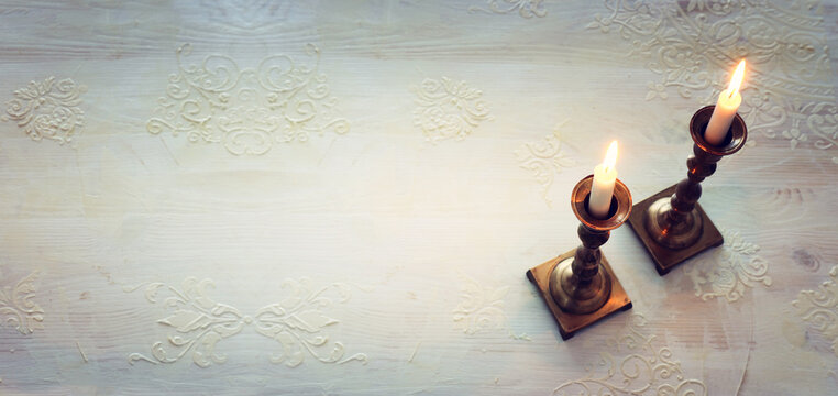 two shabbat candlesticks with burning candles over wooden table. top view