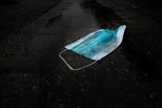Corona is over! Really...? Gebrauchte schmutzige Atemschutzmasken liegen  achtlos weggeworfen  auf nasser Straße