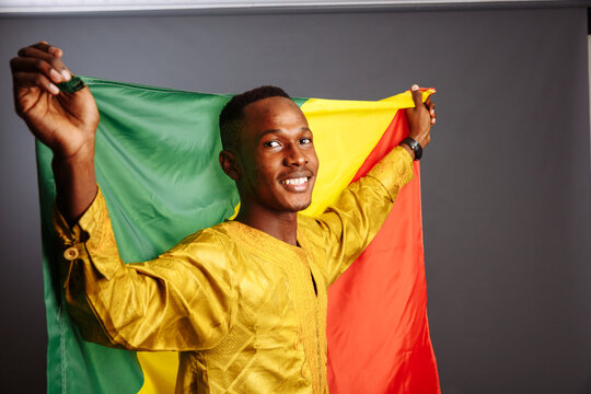 happiness african man in traditional clothes dancing with flag of Congo, isolated on gray background