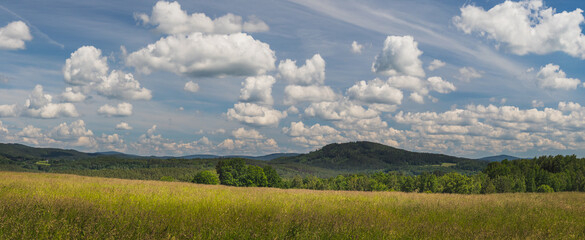 landscape with blue sky and clouds - panorama of rural countryside with field, forest and hills