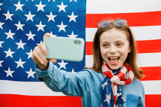 Cheerful pretty girl stands on the background of the American flag and takes pictures of herself on a mobile phone