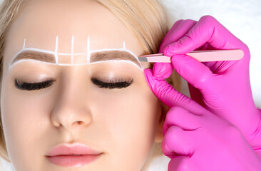 Woman Having Permanent Make-up Tattoo on her Eyebrows. Eyelash maker plucks eyebrows with tweezers. Professional makeup and cosmetology skin care.