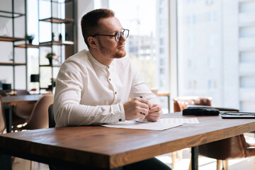 Handsome talented young composer wearing stylish eyeglasses is writing musical notes with pen on paper sheet music sitting at the wooden desk in modern room on background of large window in sunny day.