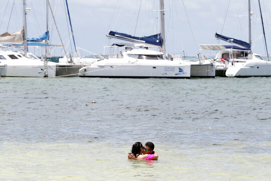Tourists embrace at a beach after local authorities imposed strict sanitary measures to gradually reopen despite the coronavirus disease (COVID-19) pandemic, in Cancun