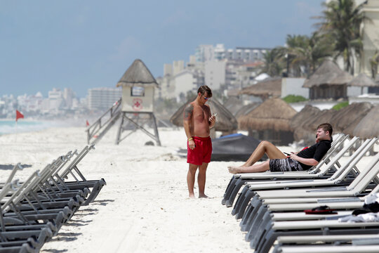 U.S. tourists relax at a beach after local authorities imposed strict sanitary measures to gradually reopen despite the coronavirus disease (COVID-19) pandemic in Cancun