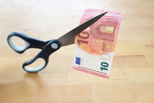 Business concept, ten Euro banknote is cut with scissors, symbol for wage reduction or pay less money in coronavirus crisis, wooden table, copy space, selected focus