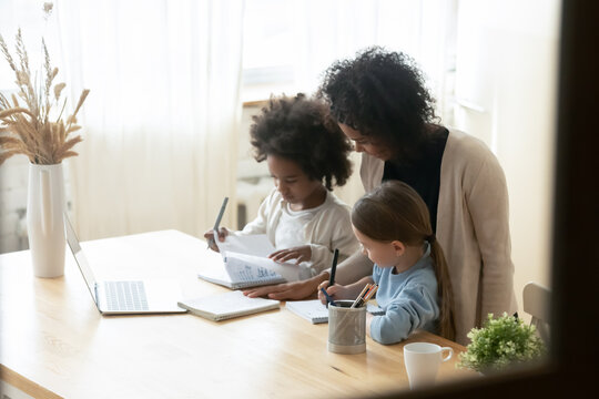 African mom of two multiethnic school age daughters do lesson homework helps them. American and Caucasian girls siblings writing on workbooks study with teacher at home. Homeschooling tutoring concept