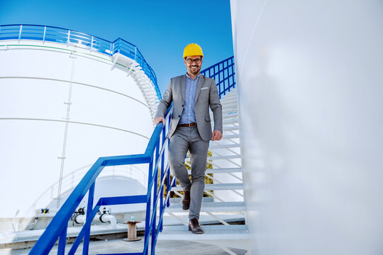 Young successful attractive caucasian businessman in suit with helmet on head going down the stairs and looking at camera. Refinery exterior.