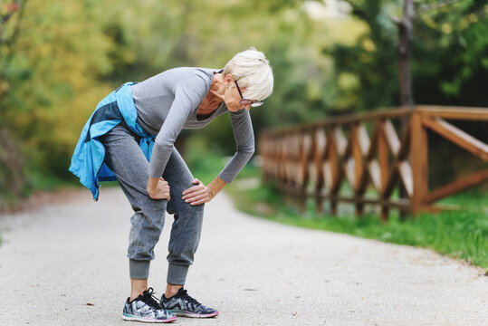 Elderly woman exercising outdoors in park with back pains