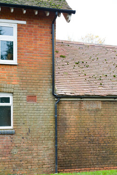 Damp wall due to leaking gutters and drainpipe, UK