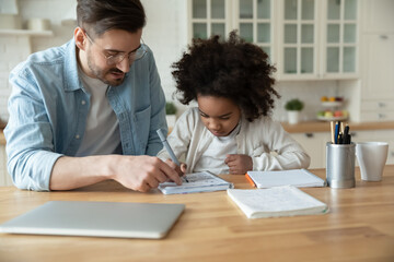 Caring Caucasian stepfather help with homework adorable mixed-race daughter. Home tutor teaches...