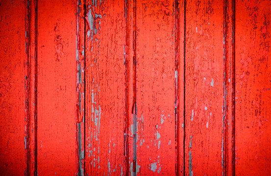 Cracked and peeling red oxidized paint on wood with texture and grunge finish