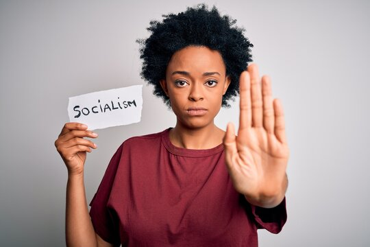 Young African American afro politician woman with curly hair socialist party member with open hand doing stop sign with serious and confident expression, defense gesture