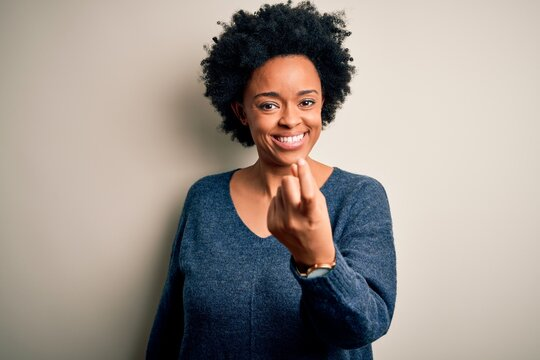 Young beautiful African American afro woman with curly hair wearing casual sweater Beckoning come here gesture with hand inviting welcoming happy and smiling