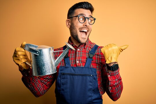 Young gardener man wearing working apron and gloves holding watering can pointing and showing with thumb up to the side with happy face smiling