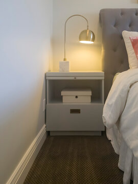 Modern lamp on top of white wood bed side table with storage drawer and shelf