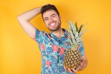 Portrait of handsome caucasian male looks with excitement at camera, keeps hands raised over head notices something unexpected, isolated over gray wall. Young man reacts on sudden news.