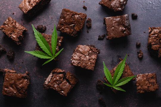 Chocolate cannabis brownies on dark background with marijuana leaf made with CBD butter. A delicious desert to impress your dinner guests and a relaxing way to end the evening.