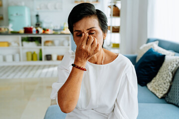 Mature Asian lady with closed eyes rubbing nose while sitting on sofa and suffering from headache in cozy living room at home