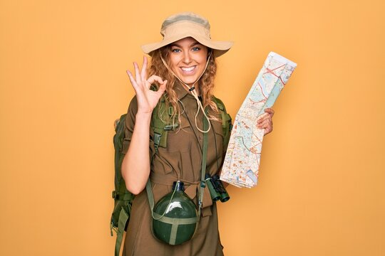 Young blonde explorer woman with blue eyes hiking wearing backpack holding city map doing ok sign with fingers, excellent symbol