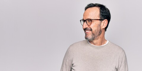 Deurstickers Ontspanning Middle age handsome man wearing casual sweater and glasses over isolated white background looking to side, relax profile pose with natural face and confident smile.