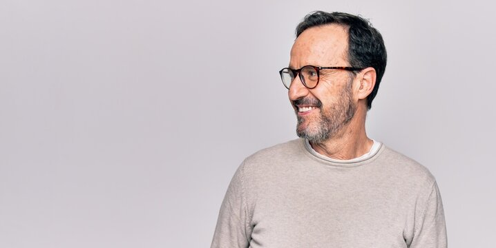 Middle age handsome man wearing casual sweater and glasses over isolated white background looking to side, relax profile pose with natural face and confident smile.