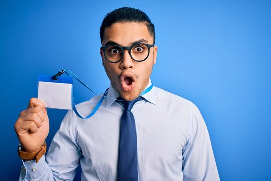 Young brazilian call center agent man holding id identification card using headset scared in shock with a surprise face, afraid and excited with fear expression
