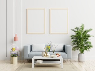 Poster mockup with vertical frame standing on floor in living room interior with sofa.