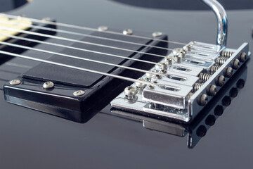 closeup to a six black electric guitar strings and microphones . Instruments and music concept