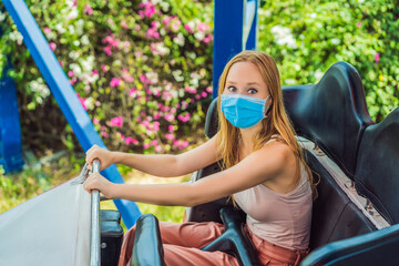 Happy friends in medical mask in an amusement park on a summer day after a coronovirus epidemic