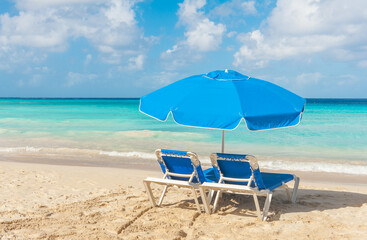 Two blue subeds with umbrella on a tropical beach near sea